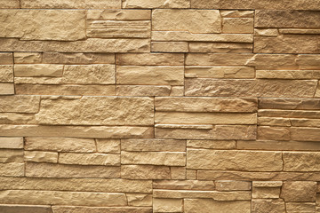 Close up abstract pattern of sandstone brick wall background in vintage tone style and vertical...