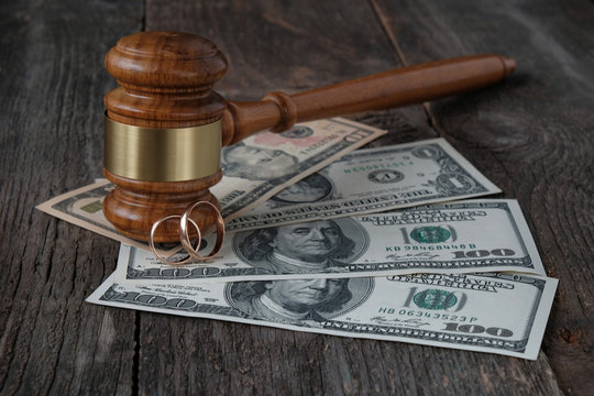 Family law concept, marriage contract, property section, judges gavel, wedding rings and money on a wooden background.