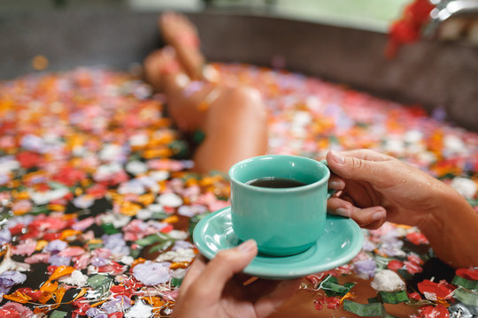 Woman in bath with petals with cup of herbal tea. Young woman relaxing in Bath with petals in tropics. Hand with cup of tea closeup