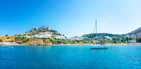 Panoramic view of Lindos beach with Acropolis of Lindos in background (Rhodes, Greece)