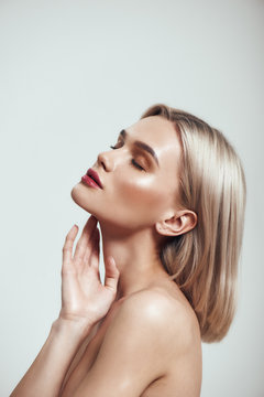 Pure beauty. Profile portrait of gorgeous young woman with blond hair and perfect shiny skin keeping eyes closed while standing against grey background