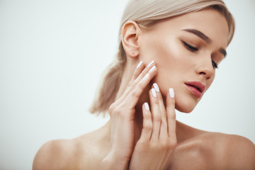 Perfect skin. Portrait of gorgeous blonde woman touching her soft glowing skin while standing against grey background