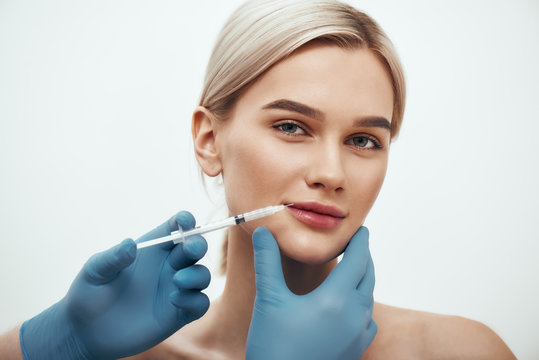 Cosmetic injection. Young beautiful woman looking at camera and smiling while doctors hand making an injection in her lips