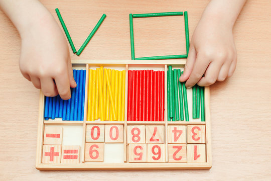 Child learning math. Early education and daycare concept. Education, school, mathematic and geometric. Colorful wooden sticks and numbers for learning.