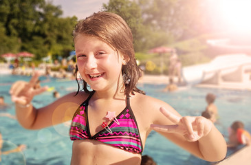 smiling little girl is enjoying in the pool in a summer day