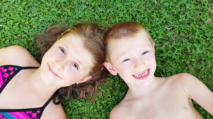 smiling children laying in the grass