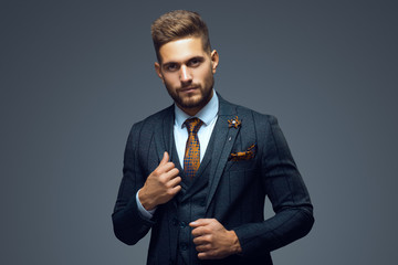 Stylish young man in suit and tie. Business style. Fashionable image. Office worker. Sexy man standing and looking at the camera Fotobehang