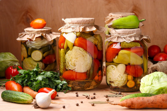 Assorted pickled vegetables in jars: cucumbers, tomatoes, cabbage, zucchini and peppers with garlic, dill and bay leaves in jars on a wooden background, horizontal photo