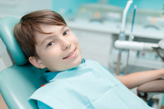 Little boy in dental chair. Smiling and satisfied patient at dentist's office after treatment. Healthy teeth, dental care concept.