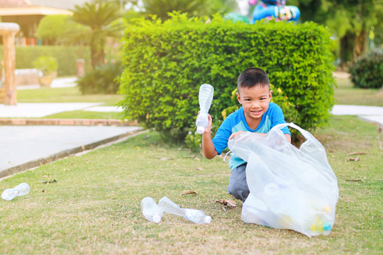 At the city public park. Asian child boy is a volunteer for clean up the field floor. He picking up many plastic bottle and straw on the ground. Save environmental and reduce waste concept.