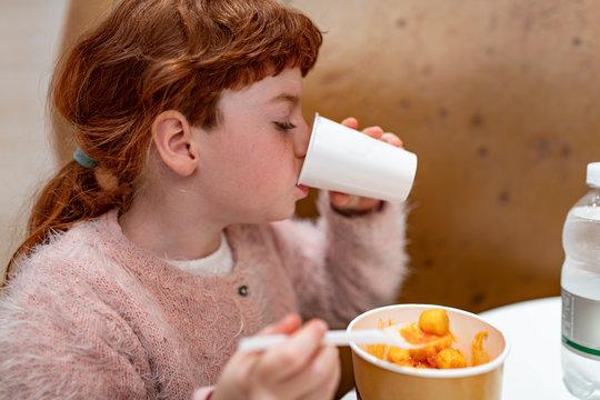 Bambina capelli rossi, che mangia e beve di gusto in una ristorazione, bar, fast food