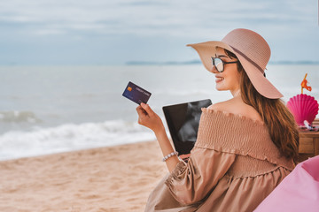 Woman use credit card  at the beach in holidays