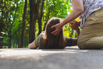 Fainted girl helped by an old woman – Teenager trying to get back on her feet while receiving support from an elder