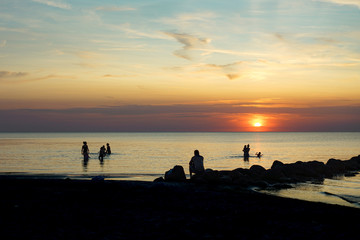 Night swimming in the ocean with a setting sun on a windless evening. Several people in silhouette.