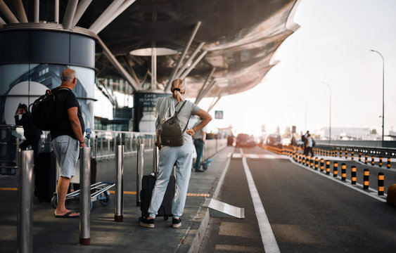 couple travelers with luggage waiting taxi in airport