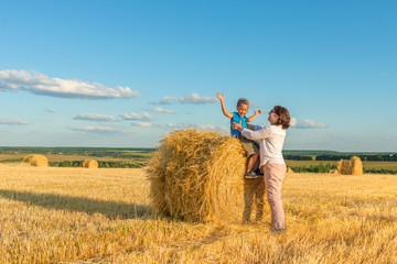 A grandmother with a grandson puts on a haystack on a field on a sunny day.  Grandson delighted, they have fun together.