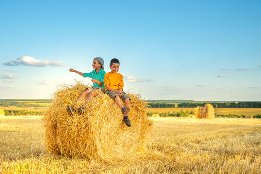 Children have fun  sit  on a haystack on a sunny day in the field.
