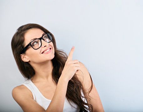 Beautiful business excited casual woman in eyeglasses pointing the finger up with toothy smiling. Closeup portrait