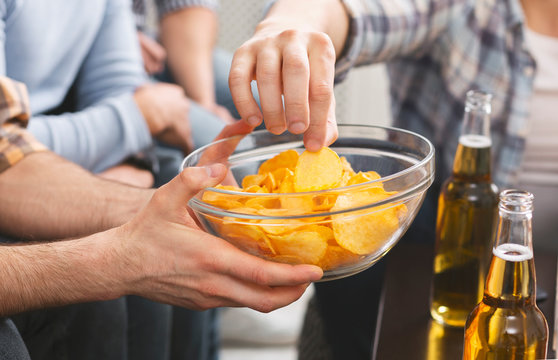 Man holding bowl with chips sharing with friends at party