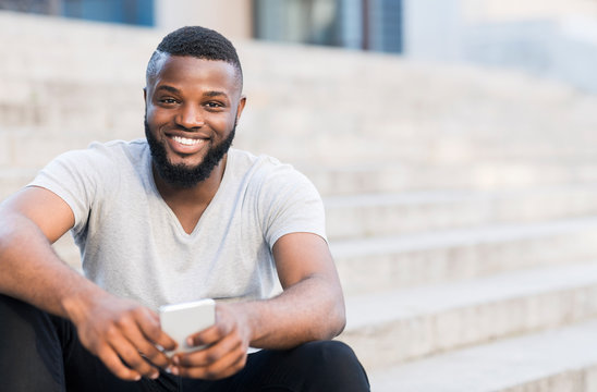 Portrait of casual african guy sitting on stairs and smiling