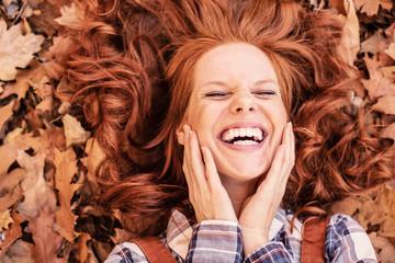rothaarige schöne Frau im Herbst mit schönen Zähnen lachend