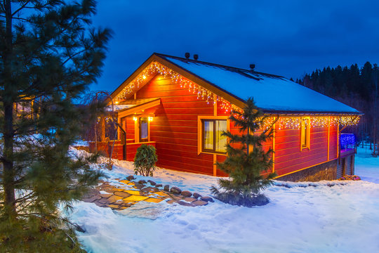 Christmas Eve. The house is decorated with garlands. Christmas holidays. Wooden house in the illumination. Winter evening. The cottage is covered with snow. Buy a house in Canada.