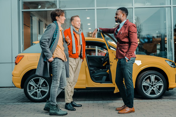 Two men talking to a car dealer after buying automobile.