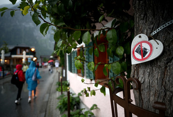 """A """"No Photography"""" sign hangs from a tree as tourists stroll down the promenade in Hallstatt, Austria"""