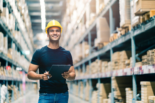 Smart Indian engineer man wearing safety helmet doing stock tick check and cardboard stock product management in factory warehouse background