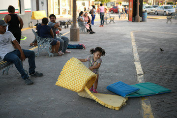 A one year-old girl from Honduras plays with a sleeping pad at a migrant encampment near the U.S. port of entry at the Gateway International Bridge in Matamoros