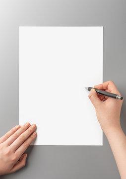 白い紙に文字を書く手