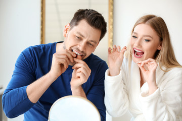 Couple flossing teeth at home