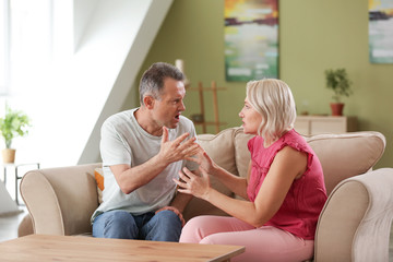 Quarrelling middle-aged couple at home