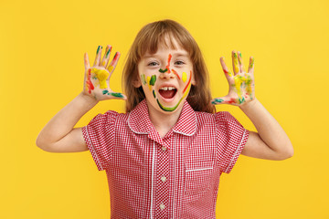 Funny little girl with hands and face in paint on color background