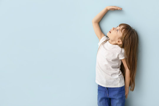 Little girl measuring height near wall