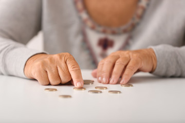 Elderly woman counting coins on table, closeup
