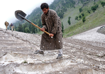 A Kashmiri Muslim man cuts snow to make way for Hindu pilgrims to trek to reach the holy Amarnath cave shrine, near Pahalgam