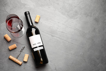Flat lay composition with delicious red wine and corks on grey table. Space for text