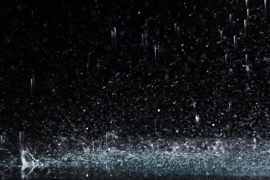 Heavy rain falling down on ground against dark background