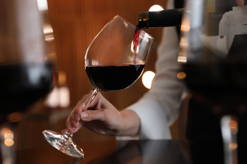 Spoed Foto op Canvas Alcohol Waitress pouring wine into glass in restaurant, closeup