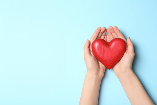 Woman holding heart on blue background, top view with space for text. Donation concept