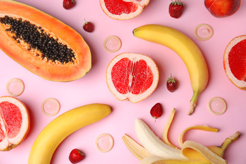 Obraz Flat lay composition with condoms and exotic fruits on pink background. Erotic concept - fototapety do salonu