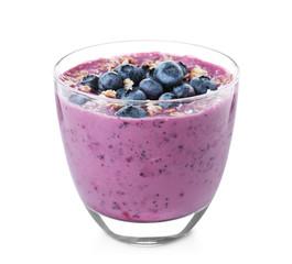 Glass of tasty blueberry smoothie with muesli on white background