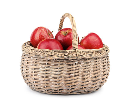 Wicker basket of ripe juicy red apples on white background
