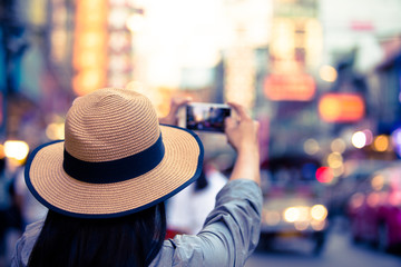 Asian tourist wearing hat is taking pictures with bokeh street lights, a woman wearing a hat, using a photo tablet, Yaowarat Road, beautiful bokeh at Yaowarat Road, Thailand.