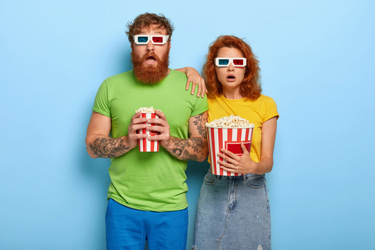 Frightened red haired woman and man being deeply impressed by film, forget they are in cinema, watch horror movie with unexpected ending, enjoy eating popcorn. This evening show grab our attention.