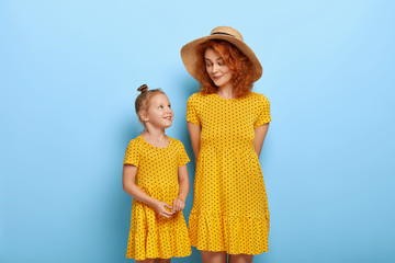 Happy loving family concept. Red haired mommy in fashionable hat and yellow dress, listens...