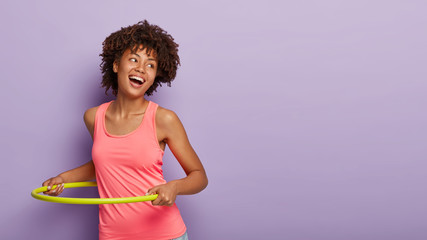 Sportive carefree woman with curly hairstyle, spins yellow plastic hoop, has gymnastic, works on figure, laughs and gazes aside, enjoys fitness activity, wears sport clothes, poses over purple wall