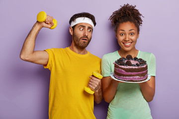 Sporty healthy lifestyle against junk food. Puzzled sportsman holds dumbbells, has fitness training, looks with temptation on delicious cake baked by wife, tries not to eat dessert with much calories