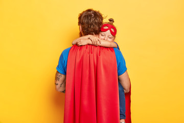 Horizontal shot of caring father carries small daughter, receives warm hug, wear red cloak and mask, play superhero game, dressed in special costumes, isolated on yellow wall. Male defender with kid